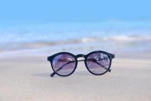 óculos de sol na praia no mar e férias de verão ao fundo do sol foto