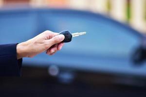 vendedor segurando a chave do carro e o carro estacionado no fundo foto