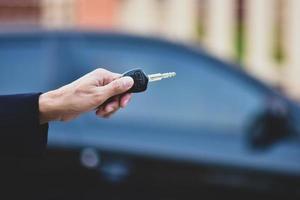 mão segurando a chave e o carro estacionado no fundo foto