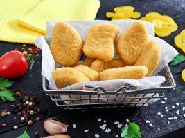 nuggets de frango crocante frito servidos com busket na madeira foto