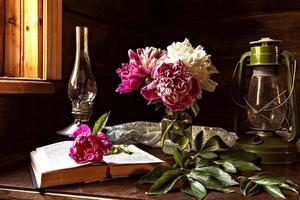 natureza morta de itens vintage e um buquê de peônias em uma mesa perto da janela em uma antiga casa de aldeia. foto