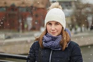 retrato de uma jovem linda feliz sorridente no fundo da cidade. moda de inverno, conceito de férias de Natal. foto