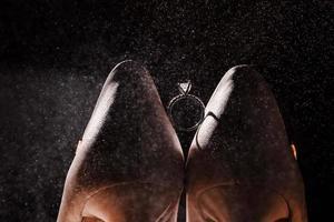 sapatos de casamento nupcial e anel com diamante. aliança entre sapatos de noiva bege com salpicos de perfume no fundo. conceito de acessórios de mulheres de casamento. foto