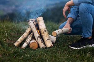 homem viajante acampando nas montanhas ao ar livre. acendendo fogo de acampamento. foto