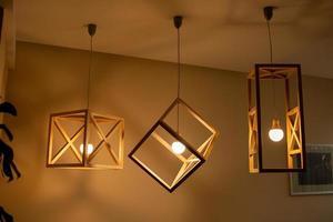lâmpadas de teto moderno lâmpada feita de moldura de madeira forma geométrica interior e decoração em estilo loft com parede de madeira branca foto