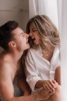 jovem casal apaixonado, aproveitando a manhã em casa perto da janela no dia dos namorados. garota de camisa branca e cara seminu se divertindo juntos foto