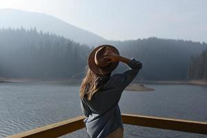 feliz jovem de chapéu goza de vista para o lago nas montanhas. momentos relaxantes na floresta. vista traseira da menina elegante aprecia o frescor ao ar livre. liberdade, pessoas, estilo de vida, viagens e férias foto