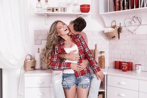 jovem casal apaixonado está se abraçando e se divertindo na cozinha no dia dos namorados pela manhã. homem elegante está beijando a mulher no pescoço e relaxando em casa. foto