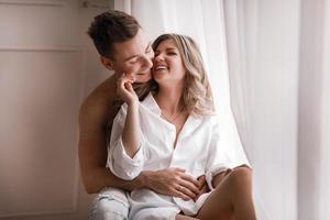 casal apaixonado se divertindo juntos em casa, esposa brincalhona mordendo a orelha do marido sorridente, nas costas, homem e mulher brincando de criança na cama, desfrutando de momentos íntimos engraçados foto