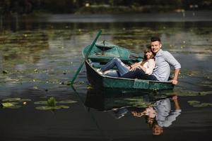 apenas relaxando. lindo casal jovem curtindo um encontro romântico enquanto remava um barco. casal apaixonado, descansando em um lago, enquanto andava em um barco verde. romance. foto