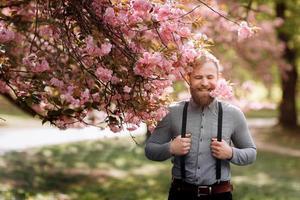 homem barbudo com corte de cabelo elegante com flores de sakura no fundo. hipster em suspensórios perto com ramo de flores de sakura nos dentes. harmonia com o conceito de natureza. foto