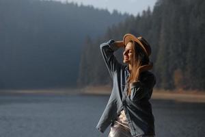 feliz jovem com chapéu goza de vista para o lago na floresta. momentos relaxantes. vista de menina elegante aprecia o frescor ao ar livre. liberdade, pessoas, estilo de vida, viagens e férias foto