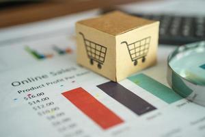 logotipo do carrinho de compras na caixa com lupa no fundo do gráfico. conta bancária, economia de dados de pesquisa analítica de investimento, comércio, conceito de empresa on-line de importação de exportação de negócios. foto