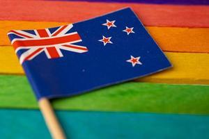 bandeira da nova zelândia no fundo do arco-íris símbolo da bandeira do movimento social do mês do orgulho gay LGBT A bandeira do arco-íris é um símbolo de lésbicas, gays, bissexuais, transgêneros, direitos humanos, tolerância e paz. foto