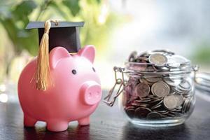 economizar moedas de dinheiro no frasco de grama com cofrinho e chapéu de formatura, conceito de educação de finanças empresariais. foto