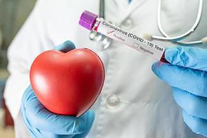 amostra de infecção de sangue positiva em tubo de ensaio para coronavírus covid-19 em laboratório. cientista segurando um coração vermelho para encorajar o paciente no hospital. foto