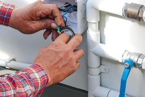 eletricista consertar o cabo de força para o controle da bomba de água no local. foto