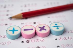 símbolo matemático e lápis no fundo da folha de respostas, conceito de ensino de aprendizagem de matemática de estudo de educação. foto