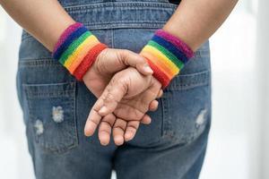 senhora asiática usando pulseiras de bandeira do arco-íris, símbolo do mês do orgulho LGBT, comemora anual em junho social de gays, lésbicas, bissexuais, transgêneros, direitos humanos. foto