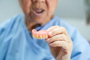 paciente asiático sênior ou idosa segurando para usar dentadura na enfermaria do hospital de enfermagem, conceito médico forte e saudável foto