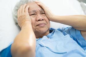 Mulher asiática sênior ou idosa idosa, dor de cabeça do paciente, enquanto está sentado na cama na enfermaria do hospital de enfermagem foto