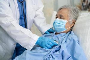 médico usando o estetoscópio para verificar o paciente asiático sênior ou idosa senhora usando uma máscara facial no hospital para proteger a infecção covid-19 coronavírus. foto