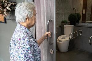 Paciente asiático sênior idosa senhora idosa banheiro aberto banheiro com a mão na enfermaria do hospital de enfermagem, conceito médico forte saudável. foto