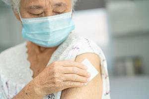 mulher idosa asiática sênior usando máscara facial recebendo vacina de covid-19 ou coronavírus pelo médico fazer injeção. foto