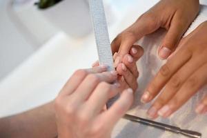 manicure unhas para o cliente sentado à mesa no escritório. foto
