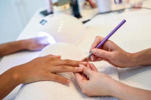 close-up de esteticista pintando as unhas de uma mulher com um pincel em um salão de beleza foto