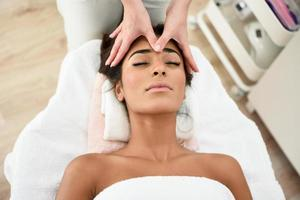 mulher recebendo massagem na cabeça no centro de bem-estar spa. foto