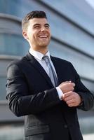 jovem empresário perto de um prédio de escritórios vestindo terno preto foto