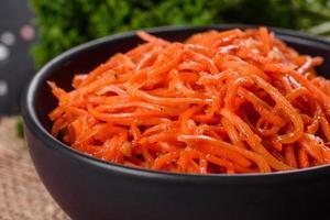 deliciosas cenouras coreanas suculentas picantes e brilhantes em pratos de cerâmica foto