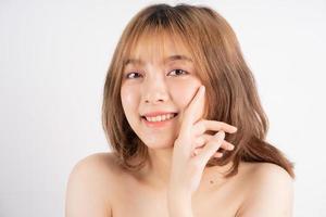 Mulher bonita com pele fresca sorrindo no fundo foto