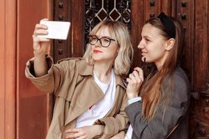 meninas tirando selfies ao telefone. fotos de selfie para redes sociais em smartphone ao fundo da rua. cara de surpresa, emoções.