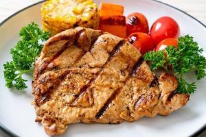 Filé de porco grelhado e grelhado com milho, cenoura e tomate foto