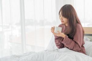 mulher asiática tomando café na cama pela manhã foto