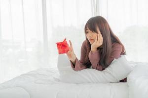 mulher asiática feliz em receber uma caixa de presente ou presente foto
