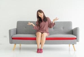 mulher asiática no sofá da sala com espaço de cópia foto
