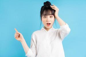 linda mulher asiática em pé apontando sobre um fundo azul com expressão de surpresa foto