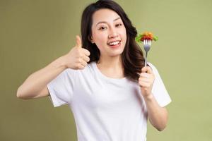 jovem asiática alegre comendo alimentos saudáveis no fundo foto