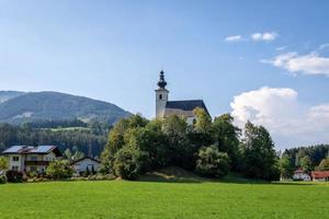 vila com uma igreja no vale alpino perto de salzburg. Áustria foto