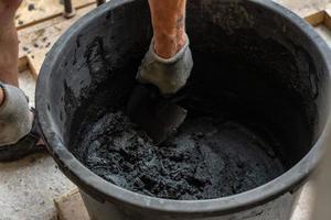 mans mão segurar uma espátula e cimento misturado no balde. foto
