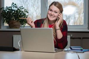 uma mulher loira sorridente, sentado em um laptop e falando ao celular. foto