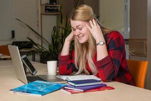 uma mulher loira sentada em um laptop quebrado e preocupada. foto