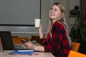 mulher loira sorridente, sentado em um laptop, bebendo chá e trabalhando. foto