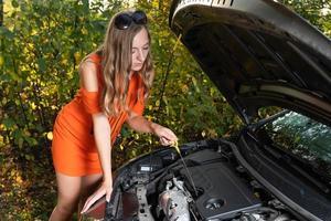 problemas com o carro. a mulher verifica o nível de óleo do motor. foto