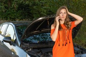 jovem perto de um carro quebrado, falando ao telefone, precisa de ajuda - imagem foto