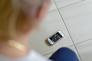 smartphone quebrado no chão de ladrilho foto