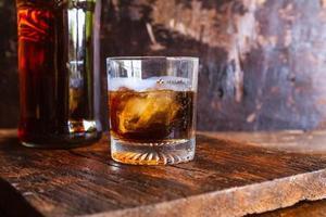 copo de licor e decantador na mesa de madeira foto